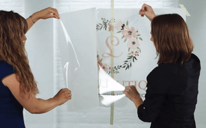 two girls peeling off the backing of a decal